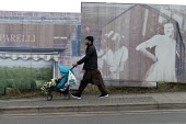 Man with pushchair walking past picture boards in front of house demolition, Hanley, Stoke on Trent, Staffordshire - John Harris - 2010s,2017,BAME,BAMEs,bigotry,Black,Black and White,BME,bmes,boards,building,buildings,child,CHILDHOOD,children,cities,City,deindustrialisation,deindustrialization,DEMOLISH,DEMOLISHED,demolition,devel