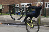 Boy pulling wheelies on his bicycle, Bentilee, Stoke on Trent, Staffordshire - John Harris - 2010s,2017,adolescence,adolescent,adolescents,bicycle,bicycles,BICYCLING,Bicyclist,Bicyclists,BIKE,BIKES,boy,boys,child,CHILDHOOD,children,cities,City,cycle,cycles,cycling,Cyclist,Cyclists,having fun,