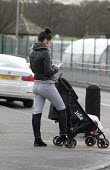 Mother and pushchair, Bentilee, Stoke on Trent, Staffordshire - John Harris - 2010s,2017,adult,adults,babies,baby,call,calls,CELLULAR,child,CHILDHOOD,children,cities,City,communicating,communication,EARLY YEARS,families,family,FEMALE,infancy,infant,infants,juvenile,juveniles,ki