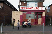 Mother, pushchair and children walking past a closed Chinese takeaway, Bentilee, Stoke on Trent, Staffordshire - John Harris - 17-02-2017