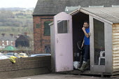 Car wash worker taking a break in a shed by a petrol station, Bentilee, Stoke on Trent, Staffordshire - John Harris - 17-02-2017