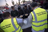 Homeless queuing for food handed out by the Imam Hasan Foodbank, Birmingham - Jess Hurd - 2010s,2016,Asian,Asians,assisting,BAME,BAMEs,Birmingham,Black,BME,bmes,charitable,charity,cities,City,curry,dining,dinner,dinners,distribution,diversity,ethnic,ethnicity,excluded,exclusion,feed,feedin