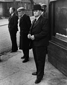 Miners dressed in their Sunday best passing the time on a street corner in a pit village waiting for the Welfare to open and for their meals to be made ready at home, County Durham, 1948 - Elisabeth Chat - 1940s,1948,capitalism,capitalist,Coal Industry,Coal Mine,coalindustry,collieries,colliery,dress,extracting,home,homes,house,houses,Housing,Industries,industry,Leisure,LFL,LIFE,maker,makers,making,male