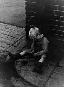 Small boy playing with coal on a street corner, Easington pit village, County Durham, 1948 - Elisabeth Chat - 1940s,1948,boy,BOYS,capitalism,capitalist,child,CHILDHOOD,children,coal,Coal Industry,Coal Mine,coalindustry,collieries,colliery,dirt dirty,excluded,exclusion,extracting,HARDSHIP,home,homes,house,hous