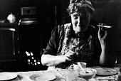 Miners wife taking a break from her domestic chores with a cup of tea and a cigarette at home, Easington pit village, County Durham, 1948 - Elisabeth Chat - 1940s,1948,break,capitalism,capitalist,CIGARETTE,cigarettes,Coal Industry,Coal Mine,coalindustry,collieries,colliery,cup of tea,domestic,excluded,exclusion,extracting,FEMALE,HARDSHIP,home,homes,house,