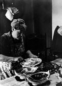 Miners wife serving dinner to her family at home, Easington pit village, County Durham, 1948 - Elisabeth Chat - 1940s,1948,BREAK,capitalism,capitalist,Coal Industry,Coal Mine,coalindustry,collieries,colliery,COOKERY,cooking,dining,dinner,dinners,DINNERTIME,domestic,domestic labour,domesticity,excluded,exclusion