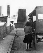 Cooperative delivering goods to a mining family, Horden pit village, County Durham, 1948. Horden Colliery can be seen in the background - Elisabeth Chat - 1940s,1948,animal,animals,bought,buy,buyer,buyers,buying,capitalism,capitalist,co operatives,Coal Industry,Coal Mine,coalindustry,collieries,colliery,commodities,commodity,consumer,consumers,cooperati