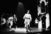 Actor John Gower centre stage in Theatre Workshop production of Oh What A Lovely War! directed by Joan Littlewood at Theatre Royal Stratford East 1963 - Romano Cagnoni - 1960s,1963,ACE,acting,actor,actors,Arts,cities,city,Culture,drama,DRAMATIC,John Gower,maker,makers,making,male,man,men,musical,Oh What A Lovely War,people,person,persons,play,PLAYING,plays,production,