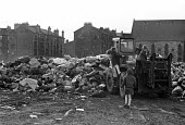 Glasgow dustcart drivers strike, 1975. Soldiers collecting rubbish. Army was sent in by Labour government to break the strike, an army bulldozer is mobbed by children - Peter Arkell - 1970s,1975,abandoned,Armed Forces,army,army strikebreaking,bag,bags,bin bag,bin bags,binbag,binbags,Black,break,British Army,bulldozer,CHILD,CHILDHOOD,children,collecting,disputes,driver,drivers,DRIVI