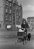 Housing in Glasgow. Young mother with tenement block behind 1975 - Peter Arkell - 1970s,1975,adult,adults,child,CHILDHOOD,children,excluded,exclusion,families,family,FEMALE,Glasgow housing,Glasgow tenements,HARDSHIP,Housing,Housing Estate,impoverished,impoverishment,INEQUALITY,juve