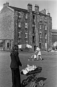 Housing in Glasgow. Young mothers with tenement block behind - Peter Arkell - 27-03-1975