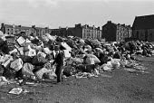 Glasgow dustcart drivers strike, 1975. Piles of rubbish in the streets, with girl playing nearby - Peter Arkell - 1970s,1975,abandoned,bag,bags,bin bag,bin bags,binbag,binbags,Black,disputes,driver,drivers,DRIVING,dump,dumped,dumping,excluded,exclusion,Glasgow,Glasgow dustcart strike,Glasgow slums,Glasgow tenemen