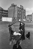 Housing in Glasgow 1975. Slum area with tenements - Peter Arkell - 1970s,1975,adult,adults,animal,animals,boy,boys,canine,child,CHILDHOOD,children,communicating,communication,conversation,conversations,dialogue,discourse,discuss,discusses,discussing,discussion,dog,do