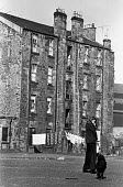 Housing in Glasgow, tenements 1975 - Peter Arkell - 1970s,1975,adult,adults,animal,animals,Broken Glass,canine,child,CHILDHOOD,children,dog,dogs,excluded,exclusion,families,family,FEMALE,Glasgow,Glasgow housing,Glasgow tenements,HARDSHIP,Housing,Housin