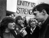Coalville 1984 Miner's wives arguing the politics of the strike with a young Paul Mason, Workers Power member. The placards proclaim the slogans Unity is Strength and Our fight is your fight. Women ag... - John Sturrock - 24-03-1984