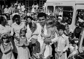 Muhammad Ali visiting Great Ormond Street Hospital London 1977. Ali holds up 2 children at the famous paediatric hospital, he was visiting the famous paediatric hospital to help raise money for it - NLA - 11-08-1977