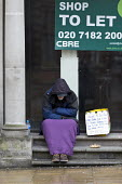 Homeless man begging in the doorway of closed shop, Leamington Spa, Warwickshire. Ex offender his sign says he will do any work offered. - John Harris - 22-03-2017