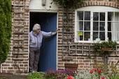 Pensioner on her doorstep, Shottery, Stratford-upon-Avon, Warwickshire - John Harris - 2010s,2017,accommodation,adult,adults,age,ageing population,doorstep,doorway,elderly,FEMALE,Front Door,garden,gardens,house,houses,housing,OAP,OAPS,old,PENSION,pensioner,pensioners,PENSIONS,people,per