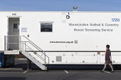 Woman attending Warwickshire Solihull & Coventry Breast Screening Service for a mammogram at a mobile clinic in a car park, Stratford-upon-Avon - John Harris - 03-04-2017