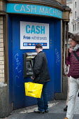 Shopper using a cash machine in Oxford Street, London - Philip Wolmuth - 2010s,2017,ATM,BAG,bags,bank,banking,banks,bought,buy,buyer,buyers,buying,Carrier Bag,cash,Cash Machine,cash point,cashmachine,cashpoint,cities,City,commodities,commodity,consumer,consumerism,consumer