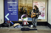 Homeless youth on the street busking, Stratford upon Avon, Warwickshire - John Harris - 2010s,2017,animal,animals,Boots the chemist,busker,buskers,busking,canine,dog,dogs,excluded,exclusion,guitar,guitars,HARDSHIP,Homeless,HOMELESSNESS,impoverished,impoverishment,INEQUALITY,male,man,Marg