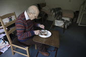 Pensioner in sheltered accommodation eating his meals on wheels lunch, Telford. Provided by a private company - John Harris - 2010s,2017,accommodation,adult,adults,age,ageing population,bedsit,bedsits,care,caring,company,dining,dinner,dinners,eat,eating,elderly,excluded,exclusion,fail,flatlets,food,FOODS,for,frailty,HARDSHIP