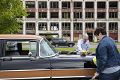 Detroit, Michigan USA Car enthusiasts polishing a 1956 Packard in front of the derelict factory where it was made. Peruvian developer Fernando Palazuelo has purchased the ruins of the Pakard plant at... - Jim West - 16-05-2017
