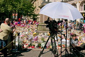 BBC News camera and umbrella in front of a large area of flowers, candles, balloons and other tributes to the victims of the Manchester Arena terrorist bomb, St Anns Square, Manchester, UK - Paul Herrmann - 26-05-2017
