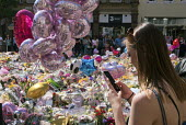Woman takes a mobile phone photo of the flowers, candles, balloons and other tributes to the victims of the Manchester Arena terrorist bomb, St Anns Square, Manchester, UK - Paul Herrmann - .,2010s,2017,activist,activists,attack,attacking,attacks,balloon,balloons,bomb,bombing,bombings,bombs,bouquet,bunch of,CAMPAIGN,campaigner,campaigners,CAMPAIGNING,CAMPAIGNS,candles,COMMEMORATE,COMMEMO