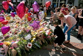 Mother and son laying flowers. Flowers, candles, balloons and other tributes to the victims of the Manchester Arena terrorist bomb, St Anns Square, Manchester, UK - Paul Herrmann - 26-05-2017