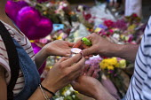 A young couple light a candle to place in tribute. Flowers, candles, balloons and other tributes to the victims of the Manchester Arena terrorist bomb, St Anns Square, Manchester, UK - Paul Herrmann - 26-05-2017