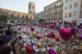 Flowers, candles, balloons and other tributes to the victims of the Manchester Arena terrorist bomb, St Anns Square, Manchester, UK - Paul Herrmann - .,2010s,2017,activist,activists,attack,attacking,attacks,balloon,balloons,bomb,bombing,bombings,bombs,bouquet,bunch of,CAMPAIGN,campaigner,campaigners,CAMPAIGNING,CAMPAIGNS,candles,church,churches,COM