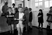 Pupils collecting their lunch, dinner time, primary school, Abbey Wood, South East London 1971 - NLA - 1970s,1971,boy,boys,canteen,CANTEENS,child,CHILDHOOD,children,cities,City,collecting,cook,cooks,dining hall,dinner,dinners,eat,eating,EDU,educate,educating,Education,educational,employee,employees,Emp