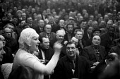 Woman speaking out at a mass meeting of mostly men, Post Office workers strike, 1971. UPW branch against the proposed settlement towards the end of the strike - NLA - 1970s,1971,against,cities,City,democracy,disputes,EARNINGS,equal rights,equality,FEMALE,feminism,feminist,feminists,Income,INDUSTRIAL DISPUTE,inequality,living wage,Low Pay,Low Income,low paid,Low Pay