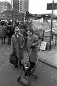 Pensioners shopping, market, London 1972 - NLA - 1970s,1972,adult,adults,age,ageing population,bought,buy,buyer,buyers,buying,commodities,commodity,communicating,communication,consumer,consumers,conversation,conversations,customer,customers,dialogue