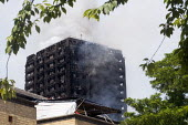 Grenfell Tower Fire. Smoke still smouldering a full 12 hours after the raging inferno that engulfed the West London tower block resulting in the loss of many lives - Stefano Cagnoni - 2010s,2017,accident,accidental,accidents,blackened,blocks,building,buildings,burn,burning,BURNS,burnt out,charred,cities,City,cladding,Council Housing,Council Housing,dead,death,deaths,destroyed,destr