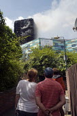 Grenfell Tower Fire. Local residents watch on as smoke still smoulders a full 12 hours after the raging inferno that engulfed the West London tower block resulting in the loss of many lives - Stefano Cagnoni - 14-06-2017