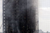 Grenfell Tower Fire. Pockets of fire still visible in some flats as smoke is seen still smouldering a full 12 hours after the raging inferno that engulfed the West London tower block seen on the left... - Stefano Cagnoni - 2010s,2017,accident,accidental,accidents,blackened,blocks,building,buildings,burn,burning,BURNS,burnt out,charred,cities,City,cladding,Council Housing,Council Housing,dead,death,deaths,destroyed,destr