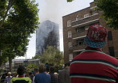 Grenfell Tower Fire. Local residents look on as smoke can be seen still smouldering a full 12 hours after the raging inferno that engulfed the West London tower block seen on the left resulting in the... - Stefano Cagnoni - 14-06-2017