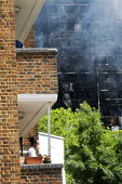 Grenfell Tower Fire. Local resident on his balcony wears a mask to filter fumes from the smoke still smouldering a full 12 hours after the raging inferno that engulfed the West London tower block seen... - Stefano Cagnoni - 2010s,2017,accident,accidental,accidents,BAME,BAMEs,Black,blocks,BME,bmes,building,buildings,burn,burning,BURNS,burnt out,cities,City,Council Housing,Council Housing,dead,death,deaths,destroyed,destru