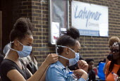 Grenfell Tower Fire. Local residents outside the Latymer Community Centre in West London just a few hundred metres from Grenfell Tower help each other don masks to protect them from the smoke and fume... - Stefano Cagnoni - 14-06-2017