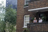 Grenfell Tower Fire. Local residents on their balcony one wearing a mask to filter fumes from the smoke still smouldering a full 12 hours after the raging inferno that engulfed the West London tower b... - Stefano Cagnoni - 14-06-2017