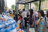 Grenfell Tower Fire. Local residents outside the Latymer Community Church Centre in West London just a few hundred metres from Grenfell Tower collect contributions donated by other local people to hel... - Stefano Cagnoni - 2010s,2017,accident,accidental,accidents,aid,assistance,assisting,BAME,BAMEs,Black,blocks,BME,bmes,bottle,bottles,Church,churches,cities,City,communities,Community,Council Housing,Council Housing,dead