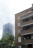 Grenfell Tower Fire. Local resident on her balcony in flats very nearby to Grenfell Tower where smoke can still be seen smouldering a full 12 hours after the raging inferno that engulfed the West Lond... - Stefano Cagnoni - 14-06-2017