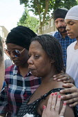 Grenfell Tower Fire. Family and friends support Aalya Moses a resident on the fourth floor of Grenfell Tower as she tells news reporters how she made her escape from the burning building which claimed... - Stefano Cagnoni - 2010s,2017,Aalya Moses,accident,accidental,accidents,BAME,BAMEs,black,BME,bmes,building,BUILDINGS,BURN,burning,BURNS,cities,City,Council Housing,Council Housing,cry,crying,dead,death,deaths,despair,de