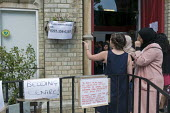 Grenfell Tower Fire. A volunteer pointing out the emergency number for missing friends to local residents as they bring donations to Notting Hill Methodist Church one of the Relief Centres set up just... - Stefano Cagnoni - 14-06-2017