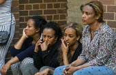 Grenfell Tower Fire. Anxious local women waiting opposite the makeshift evacuation centre at Rugby Portobello Trust for news of victims of the fire that engulfed the West London tower block overnight - Stefano Cagnoni - 2010s,2017,accident,accidental,accidents,anxiety,ANXIOUS,ANXIOUSNESS,APPREHENSIVE,BAME,BAMEs,black,BME,bmes,call,calls,CELLULAR,cities,City,communicating,communication,communities,community,Council Ho