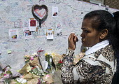 Woman in tears beside the Wall of condolence a few hundred metres from the Grenfell Tower fire filled with messages of love and solidarity in memory of the victims of the tragedy, London - Stefano Cagnoni - 2010s,2017,accident,accidental,ACCIDENTS,anger,BAME,BAMEs,Black,blocks,BME,bmes,bouquet,bunch of,cities,City,COMMEMORATE,COMMEMORATING,commemoration,COMMEMORATIONS,commemorative,condolence,Council Hou