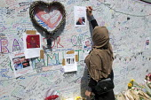 Woman writing a message on the Missing Poster of Hesham Rahman on the Wall of condolence a few hundred metres from the Grenfell Tower fire filled with messages of love and solidarity in memory of the... - Stefano Cagnoni - 16-06-2017