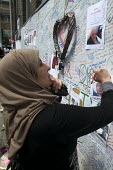 Woman writing a message on the Missing Poster of Hesham Rahman on the Wall of condolence a few hundred metres from the Grenfell Tower fire filled with messages of love and solidarity in memory of the... - Stefano Cagnoni - 2010s,2017,accident,accidental,ACCIDENTS,anger,BAME,BAMEs,Black,blocks,BME,bmes,bouquet,cities,City,COMMEMORATE,COMMEMORATING,commemoration,COMMEMORATIONS,commemorative,condolence,Council Housing,Coun
